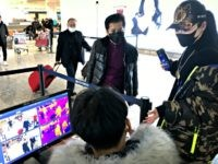 FILE - In this Jan. 21, 2020, file photo, travelers pass through a health screening checkpoint at Wuhan Tianhe International Airport in Wuhan in southern China's Hubei province. For weeks after the first reports of a mysterious new virus in Wuhan, people poured out of the central Chinese city, cramming …