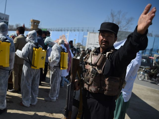 An Afghan policeman gestures as volunteers wearing a hazmat suits and a facemasks gather on before the start of a preventive campaign against the spread of the COVID-19 coronavirus, in Kabul on March 18, 2020. (Photo by WAKIL KOHSAR / AFP) (Photo by WAKIL KOHSAR/AFP via Getty Images)