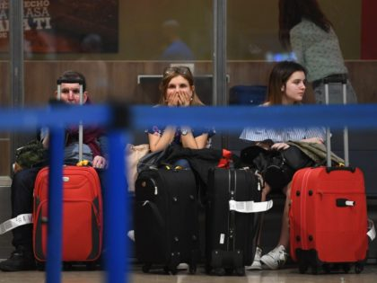 Passengers wait near the Ryanair check-in counters at Adolfo Suarez Madrid Barajas airport on July 25, 2018 as the airline's cabin crew began a two-day strike. - Ryanair has been forced to cancel dozens of flights across Europe as its cabin crew began a two-day strike in Spain, Portugal Belgium …
