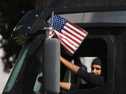 LOS ANGELES, CA - NOVEMBER 13: A trucker drives near City Hall to protest shipping container fees being assessed against independent truckers as part of the ports' Clean Truck Program to allow only newer, less-polluting trucks at the ports, on November 13, 2009 in Los Angeles, California. The members of …