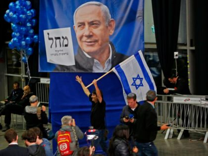 A man reacts as he holds up an Israeli flag while standing behind a giant Likud party election poster showing the face of its leader Prime Minister Benjamin Netanyahu at the Likud's electoral headquarters in the coastal city of Tel Aviv on March 2, 2020, after polls officially closed. - …