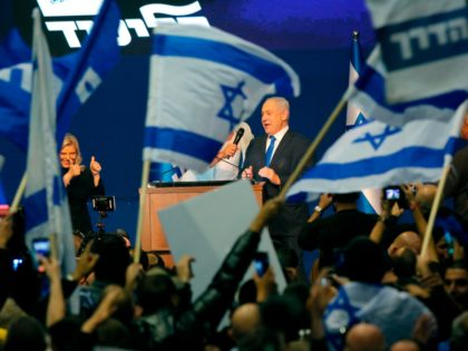 """Israeli singer Regev Hod (unseen) holds a microphone for Prime Minister Benjamin Netanyahu as he and his wife appear before supporters at the Likud party campaign headquarters in the coastal city of Tel Aviv early on March 3, 2020, after polls officially closed. - Netanyahu claimed """"a giant victory"""" in …"""