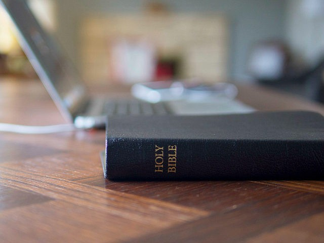 A Bible next to a laptop computer. Speaking of the work of the ministry and how technology and the Bible are closely connected.