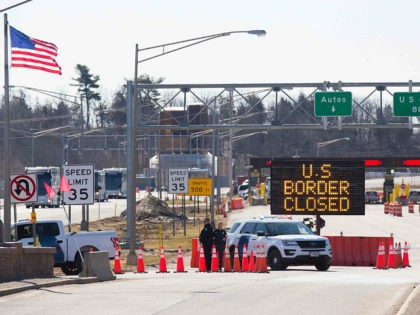 TOPSHOT - US Customs officers stand beside a sign saying that the US border is closed at the US/Canada border in Lansdowne, Ontario, on March 22, 2020. - The United States agreed with Mexico and Canada to restrict non-essential travel because of the coronavirus, COVID-19, outbreak and is planning to …