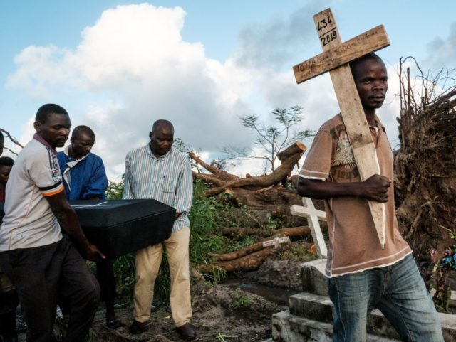 TOPSHOT - People carry the coffin of Tomas Joaquim Chimukme during his funeral, after his home collapsed following a strong cyclone that hit Beira, Mozambique, on March 20, 2019. - Five days after tropical cyclone Idai cut a swathe through Mozambique, Zimbabwe and Malawi, the confirmed death toll stood at …