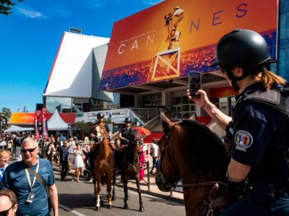 A Mounted Police female officer (R) takes photos of fellow policemen as they patrol on horseback outside the Festival Palace during the 72nd edition of the Cannes Film Festival in Cannes, southern France, on May 14, 2019. (Photo by Laurent EMMANUEL / AFP) (Photo by LAURENT EMMANUEL/AFP via Getty Images)