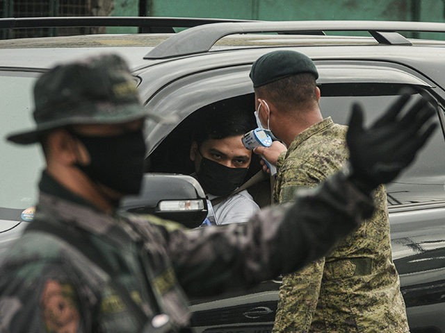 A soldier checks the temperature of a motorist at a checkpoint before entering Manila on March 16, 2020, as part of measures to reduce the spread of the COVID-19 pandemic. - The virus has upended society around the planet, with governments imposing restrictions rarely seen outside war-time, including the closing …