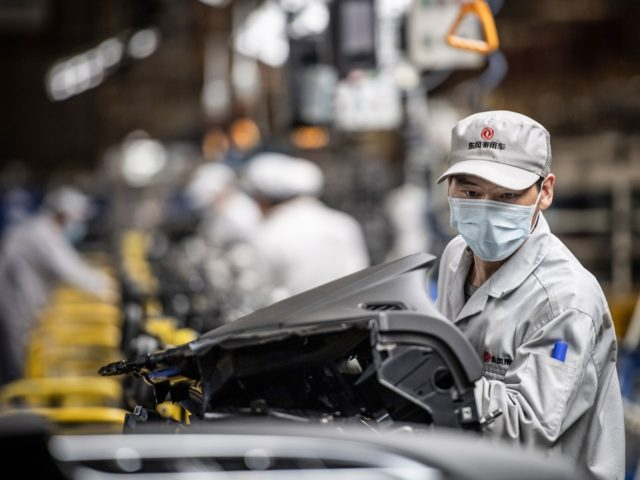 This photo taken on March 23, 2020 shows an employee wearing a face mask working on an assembly line at an auto plant of Dongfeng Honda in Wuhan in China's central Hubei province. - People in central China, where the COVID-19 coronavirus was first detected, are now allowed to go …