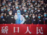 TOPSHOT - Members of a medical assistance team from Jiangsu province chant slogans at a ceremony marking their departure after helping with the COVID-19 coronavirus recovery effort, in Wuhan, in China's central Hubei province on March 19, 2020. - Medical teams from across China began leaving Wuhan this week after …