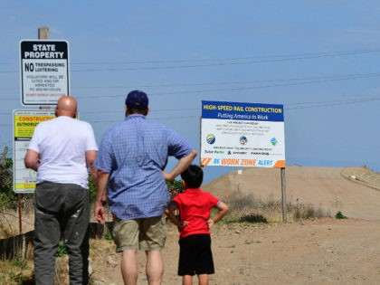 People read signs near a constuction site off Avenue 12 in Madera, California just north of Fresno on the California High Speed-Railway on May 5, 2019. - For more than five years residents and businesses have been disrupted and relocated up and down California's central San Joaquin Valley from the …