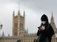 A pedestrian wearing a face mask walks along Westminster Bridge in front of the Houses of Parliament in London on March 12, 2020. - The British government was expected Thursday to implement the second phase of its plan to deal with the coronavirus outbreak but rejected calls for parliament to …