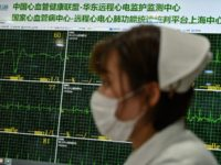 A nurse walks in an area where doctors take video calls from patients suffering various symptoms and illnesses, to avoid crowding at Xuhui District Hospital in Shanghai on March 9, 2020. - China reported 22 new deaths on March 9 from the new coronavirus epidemic, and the lowest number of …