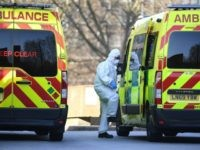 A member of the ambulance service wearing personal protective equipment is seen leading a patient (unseen) into an ambulance at St Thomas' Hospital in London on March 24, 2020. - Britain's leaders on Tuesday urged people to respect an unprecedented countrywide lockdown, saying that following advice to stay at home …