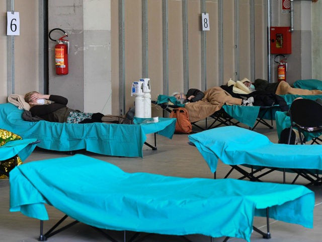 Patients lie in bed at a temporary emergency structure set up outside the accident and emergency department, where any new arrivals presenting suspect new coronavirus symptoms are being tested, at the Brescia hospital, Lombardy, on March 13, 2020. (Photo by Miguel MEDINA / AFP) (Photo by MIGUEL MEDINA/AFP via Getty …
