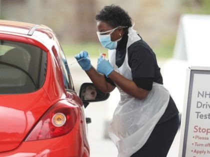 CHESSINGTON, UNITED KINGDOM - MARCH 30: A nurse takes a swab at a Covid-19 Drive-Through testing station for NHS staff on March 30, 2020 in Chessington, United Kingdom. The Coronavirus (COVID-19) pandemic has spread to many countries across the world, claiming over 30,000 lives and infecting hundreds of thousands more. …