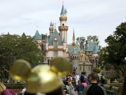 FILE - In this Jan. 22, 2015, file photo, visitors walk toward Sleeping Beauty's Castle in the background at Disneyland Resort in Anaheim, Calif. Disneyland says it's closing its California parks starting Saturday over coronavirus concerns. For most people, the new coronavirus causes only mild or moderate symptoms. For some …