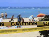 In this Friday, March 20, 2020, file photo, as beachgoers are seen in the background, yellow caution tape wrapped across Waikiki in Honolulu. Hawaii's governor has instituted a mandatory 14-day self quarantine starting Thursday, March 27, of all people traveling to the state as part of efforts to fight the …