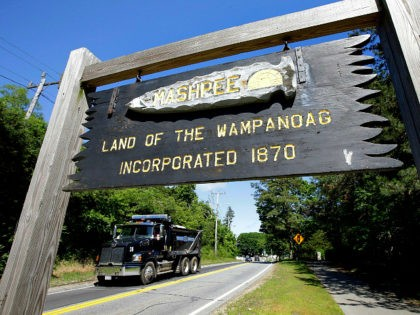 In this Monday, June 25, 2018 photo a wooden sign advises motorists of the location of Mashpee Wampanoag Tribal lands in Massachusetts. The Mashpee Wampanoag Tribe says an unfavorable decision from the U.S. Interior Department on its tribal reservation status would effectively shut down certain government operations, including the tribe's …
