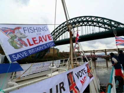 Fishing vessels are moored near the Tyne Bridge in Newcastle, northeast England on April 8, 2018, during a protest against the Brexit transition deal that would see Britain continue to adhere to the Common Fisheries Policy after formally leaving the EU, People working in the fishing industry supported by the …