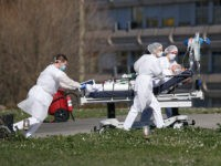 A victim of the Covid-19 virus is evacuated from the Mulhouse civil hospital, eastern France, Monday March 23, 2020. The Grand Est region is now the epicenter of the outbreak in France, which has buried the third most virus victims in Europe, after Italy and Spain. For most people, the …
