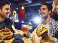 Happy friends eat burgers, drink beer in a bar. People in a fast food restaurant.