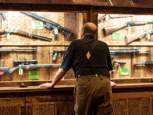 FILE - In this April 25, 2019, file photo, a man looks at cases of firearms in the halls of the Indianapolis Convention Center where the National Rifle Association will be holding its 148th annual meeting in Indianapolis. The number of background checks conducted by federal authorities is on pace …