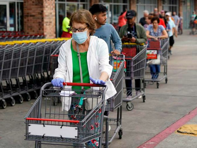 Ruth Flavelle wears a mask and gloves as she enters an H-E-B grocery after waiting in line with more than 150 people Tuesday, March 17, 2020, in Spring, Texas. Grocery store executives and city officials reassured the community, on Monday, that plenty of food will be available in their stores …
