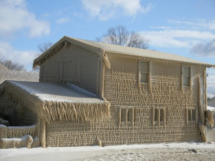 Houses along Hoover Beach are covered by ice from high winds and fifteen foot Lake Erie waves, Saturday, Feb. 29, 2020, in Hamburg N.Y. (AP Photo/Jeffrey T. Barnes)