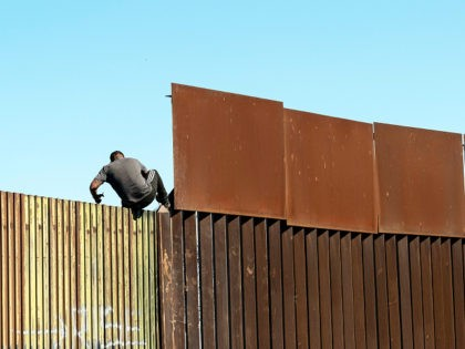 TOPSHOT - A man crosses over the US/Mexico border fence from Mexicali to Calexico, at Mexicali, Baja California state, Mexico, on February 11, 2020. (Photo by Guillermo Arias / AFP) (Photo by GUILLERMO ARIAS/AFP via Getty Images) coronavirus