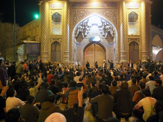 People gather outside the closed doors of the Fatima Masumeh shrine in Iran's holy city of Qom on March 16 2020. - Iran closed four key Shiite pilgrimage sites across the Islamic republic on March 16 in line with measures to stop the spread of the new coronavirus, state media …