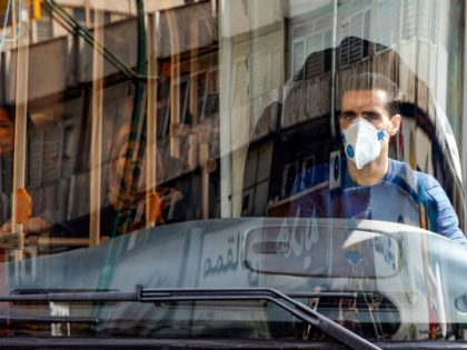 A bus driver wearing a protective mask as a precaution against COVID-19 coronavirus disease operates a bus in Iran's capital Tehran on March 15, 2020. (Photo by STRINGER / AFP) (Photo by STRINGER/AFP via Getty Images)