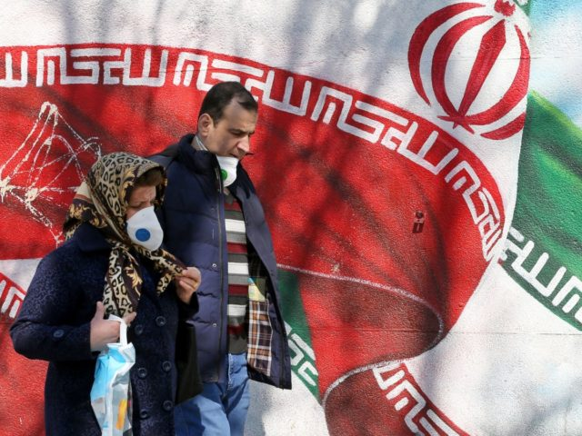 Iranians wearing masks walk past a mural displaying their national flag in Tehran on March 4, 2020. - Iran has scrambled to halt the rapid spread of the COVID-19 virus, shutting schools and universities, suspending major cultural and sporting events, and cutting back on work hours. (Photo by ATTA KENARE …