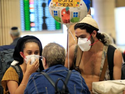A young couple wearing protective masks are greeted upon arrival at Ben Gurion airport in Israel's coastal city of Tel Aviv on March 4, 2020. - Israel ordered a two-week quarantine on people arriving from France, Germany, Spain, Austria and Switzerland over coronavirus fears, after imposing similar measures on Italy …