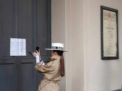 A woman takes a picture of a notice on the entrance doors, written in Italian and English, advising that La Scala theater performances are suspended due to the spread of coronavirus, in Milan, Italy, Sunday, Feb. 23, 2020. In Lombardy, the hardest-hit region with 90 cases, schools and universities were …
