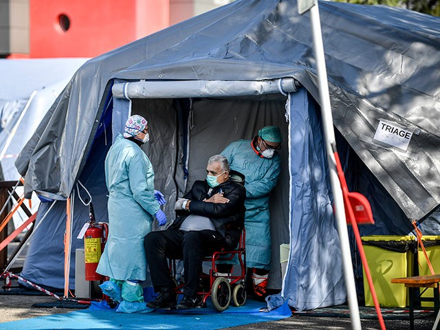 An elderly patient is attended in one of the emergency structures that were set up to ease procedures outside the hospital of Brescia, Northern Italy, Tuesday, March 10, 2020. For most people, the new coronavirus causes only mild or moderate symptoms, such as fever and cough. For some, especially older …