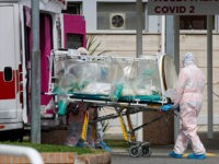 A patient in a biocontainment unit is carried from an ambulance arrived at the Columbus Covid 2 Hospital in Rome, Tuesday, March 17, 2020. For most people, the new coronavirus causes only mild or moderate symptoms. For some it can cause more severe illness, especially in older adults and people …