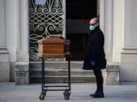A man stands by the coffin of his mother during a funeral service in the closed cemetery of Seriate, near Bergamo, Lombardy, on March 20, 2020 during the country's lockdown aimed at stopping the spread of the COVID-19 (new coronavirus) pandemic. (Photo by Piero Cruciatti / AFP) (Photo by PIERO …