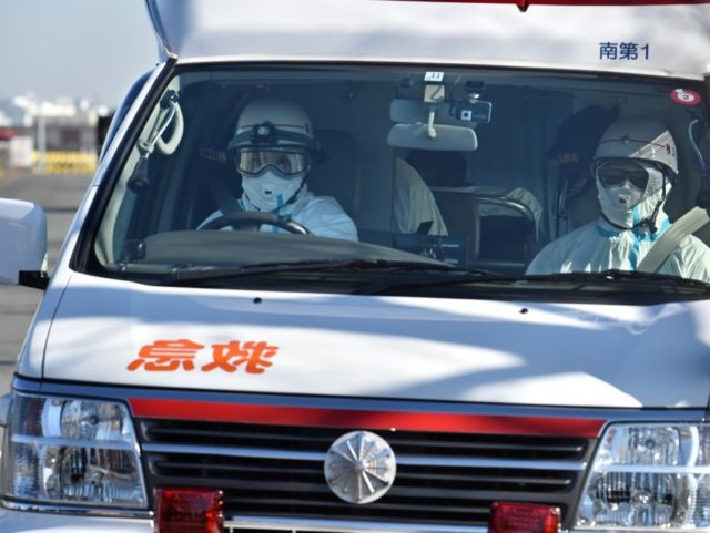 TOPSHOT - An ambulance departs the Japan Coast Guard base in Yokohama on February 5, 2020 after bringing patients from the Diamond Princess cruise ship. - At least 10 people on a cruise ship quarantined off the coast of Japan have tested positive for the new coronavirus, Japan's health minister …