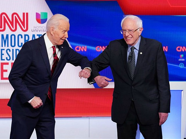 Democratic presidential hopefuls former US vice president Joe Biden (L) and Senator Bernie Sanders (R) greet each other with an elbow bump as they arrive for the 11th Democratic Party 2020 presidential debate in a CNN Washington Bureau studio in Washington, DC on March 15, 2020. (Photo by MANDEL NGAN …