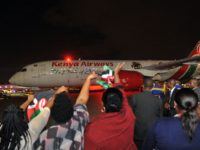 People wave Kenyan flags as a Boeing 787-Dreamliner of Kenya Airways taxis out to the runway following a flag-off ceremony attended by the Kenyan President as it embarks on the airline's first ever non-stop flight from Jomo Kenyatta International Airport in Nairobi to New York on October 28, 2018. - …