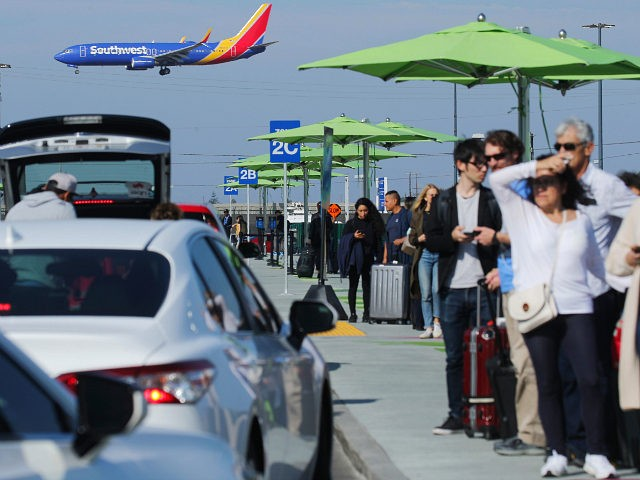 LOS ANGELES, CALIFORNIA - NOVEMBER 06: Arriving passengers wait to board Uber vehicles at the new 'LAX-it' ride-hail passenger pickup lot, as a Southwest Airlines plane lands, at Los Angeles International Airport (LAX) on November 6, 2019 in Los Angeles, California. The airport has instituted a ban on Lyft, Uber …