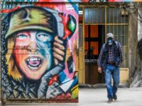 A Lebanese man, wearing facial gas mask as part of health safety measures related to the spread of COVID-19, walks past a graffiti in the northern port city of Tripoli, on March 16, 2020 - Lebanon, on March 15, urged people to stay at home for two weeks and prepared …
