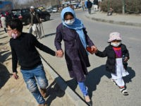 A woman with children wearing facemasks as a protective measure against the spread of the COVID-19 coronavirus, walk along a street in Kabul on March 18,2020. (Photo by WAKIL KOHSAR / AFP) (Photo by WAKIL KOHSAR/AFP via Getty Images)