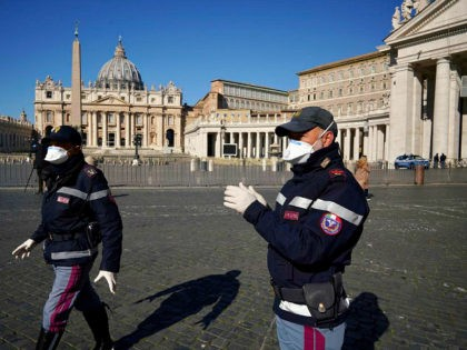 Police officers wearing masks patrol an empty St. Peter's Square at the Vatican, Wednesday, March 11, 2020. Pope Francis held his weekly general audience in the privacy of his library as the Vatican implemented Italy's drastic coronavirus lockdown measures, barring the general public from St. Peter's Square and taking precautions …