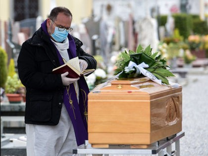 A priest wearing a face mask checks a book of funeral rites as he gives the last blessing to a deceased person, by a coffin during a funeral ceremony outside the cemetery of Bolgare, Lombardy, on March 23, 2020 during the COVID-19 new coronavirus pandemic. (Photo by Piero CRUCIATTI / …