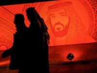 A picture taken on January 31, 2020 shows young Saudis walking next to a portrait of Crown Prince Mohammed bin Salman at the Riyadh Season Boulevard in the Saudi capital. - In Saudi Arabia's rigid past, religious police once swooped down on rose sellers and anyone peddling red paraphernalia around …