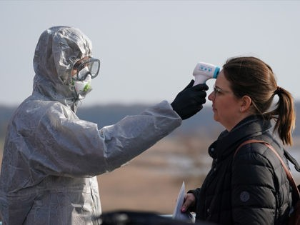 SLUBICE, POLAND - MARCH 17: A Polish border guard dressed in a protective suit, mask and goggles takes the body temperature of a Polish woman seeking to enter Poland as an indication of possible coronavirus infection at the Polish/German border at Slubice/Frankfurt (Oder) on March 17, 2020 at Slubice, Poland. …