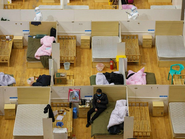 TOPSHOT - This photo taken on March 5, 2020 shows a medical worker a(top L) walking past empty beds as a patient rests at a temporary hospital set up for COVID-19 coronavirus patients in a sports stadium in Wuhan, in China's central Hubei province. - Many patients have been discharged …