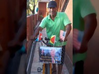 Cuban dissident Daniel Llorente, forced into exile in Guyana, with his bicycle, sporting a photo of Donald Trump and an American flag.