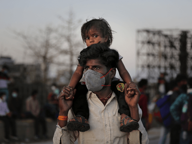 An Indian migrant worker carries a child on his shoulders as they wait for transportation to their village following a lockdown amid concern over spread of coronavirus in New Delhi, India, Saturday, March 28, 2020. Authorities sent a fleet of buses to the outskirts of India's capital on Saturday to …